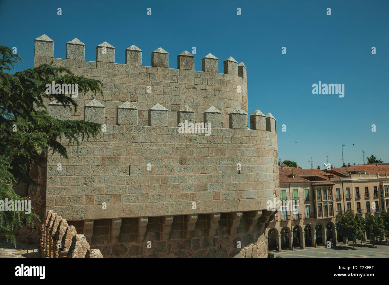 Battlement with merlons and crenels over stone tower and rooftops on buildings at Avila. With an imposing wall around the gothic city center in Spain. - Stock Image