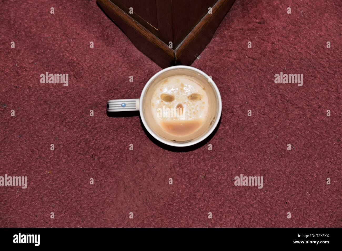 A white cup with a smiley face designed with lemon pip eyes and coffee dregs mouth. A fun creation to amuse children and folk in a festive mood. Stock Photo