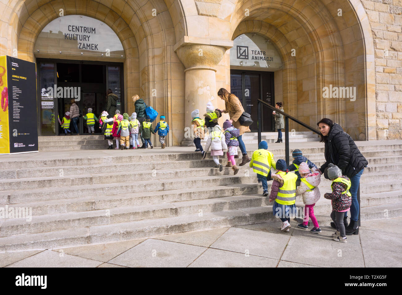 Young school children boys and girls wearing high vis jackets and clothing being led in a crocodile by teachers into the theater in Poznan Poland - Stock Image
