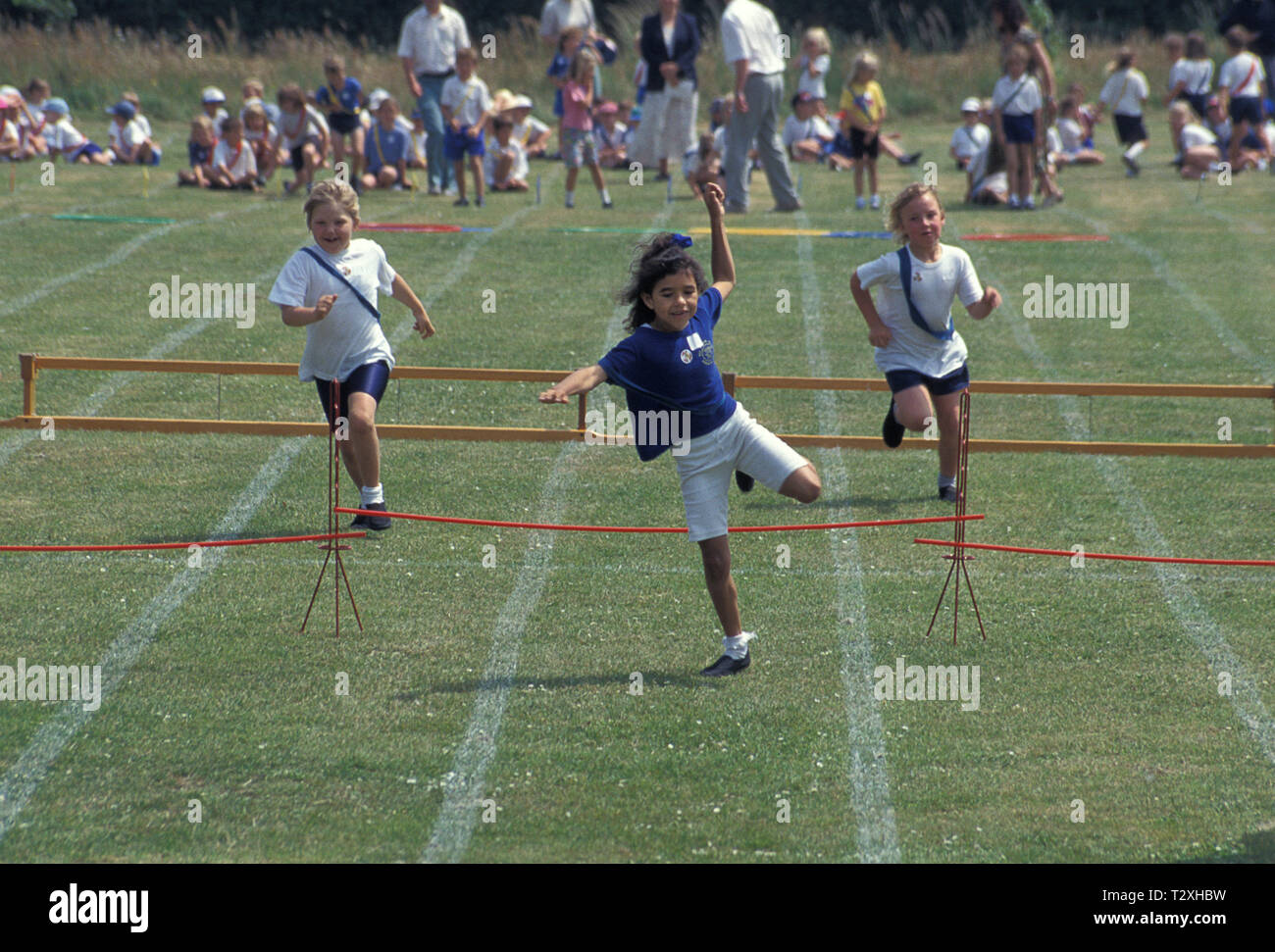 primary school children competing in hurdle race during sports day Stock Photo