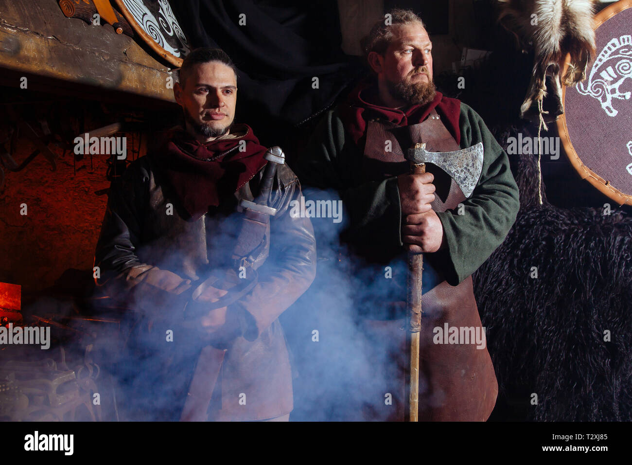 Two men in a warrior's clothes is in the smithy on the background of fire and with smoke. Serious militant Viking stands with a weapon in his hands. - Stock Image