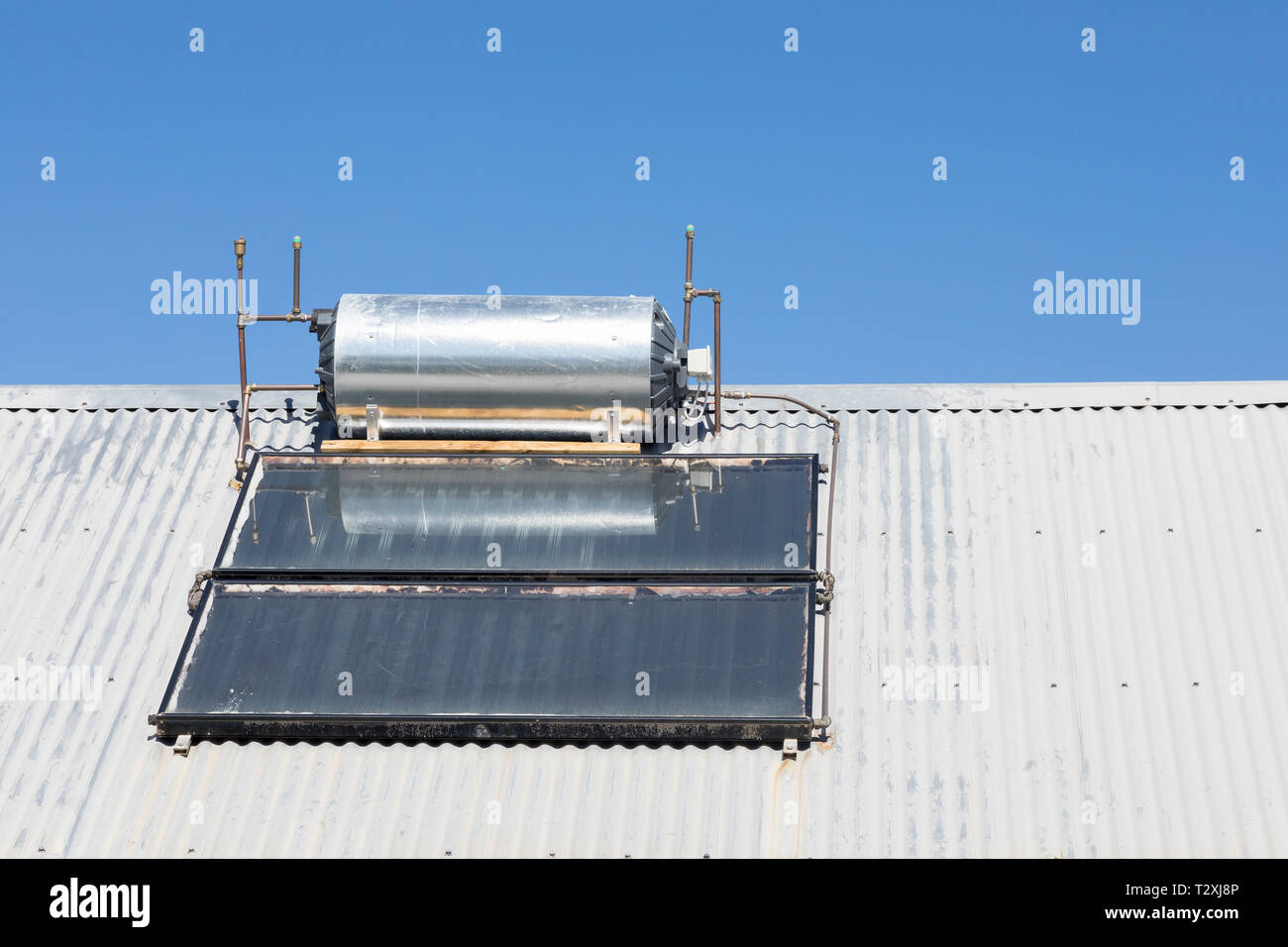 Roof mounted, rooftop, domestic solar hot water geyser with photovoltaic panels and convertor, renewable, sustainable, alternative, eco-friendly energ - Stock Image