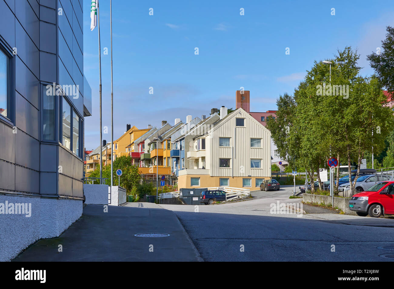 A Small street in Kristiansund in Norway with the colourful terraced houses built on a side of a hill with many tree's on a Summers day. Norway - Stock Image