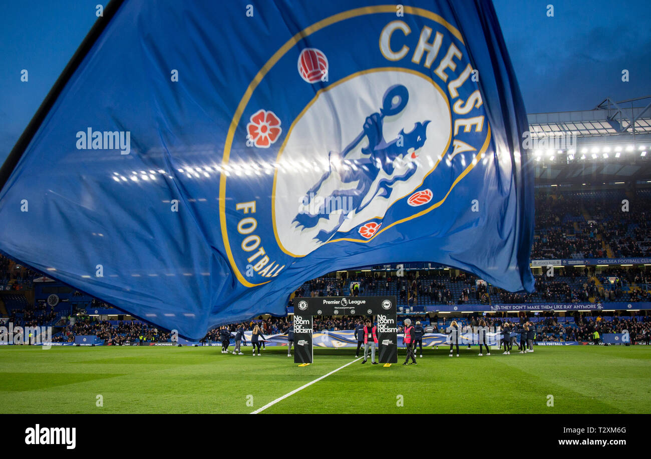 The Chelsea flag is waved with NO ROOM FOR RACISM boarding in background as players enter the pitch pre match during the Premier League match between  - Stock Image