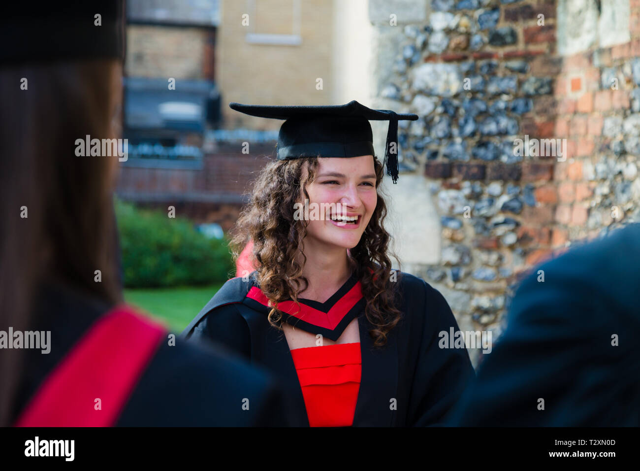 A happy student meets up with friends at a graduation ceremony at Chelmsford Cathedral. - Stock Image