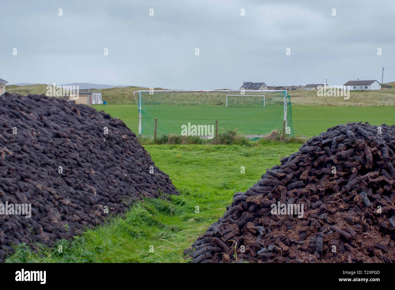 Two stacks of peat sods beside amateur soccer pitch in the west of Ireland. - Stock Image