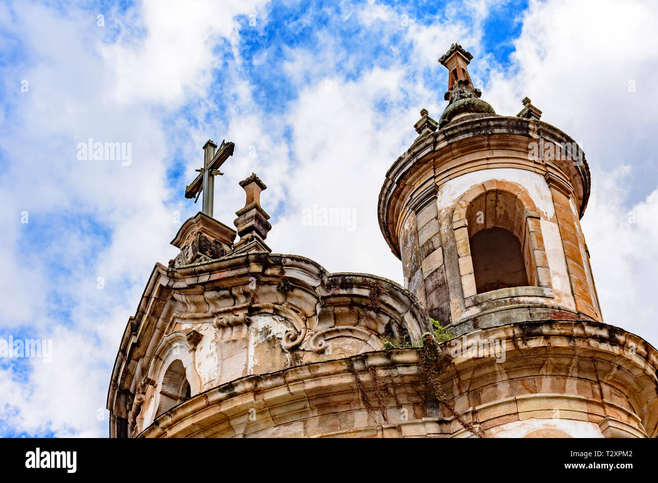Old catholic church tower, ornaments and crucifix of the 18th century located in the center of the famous and historical city of Ouro Preto in Minas G - Stock Image