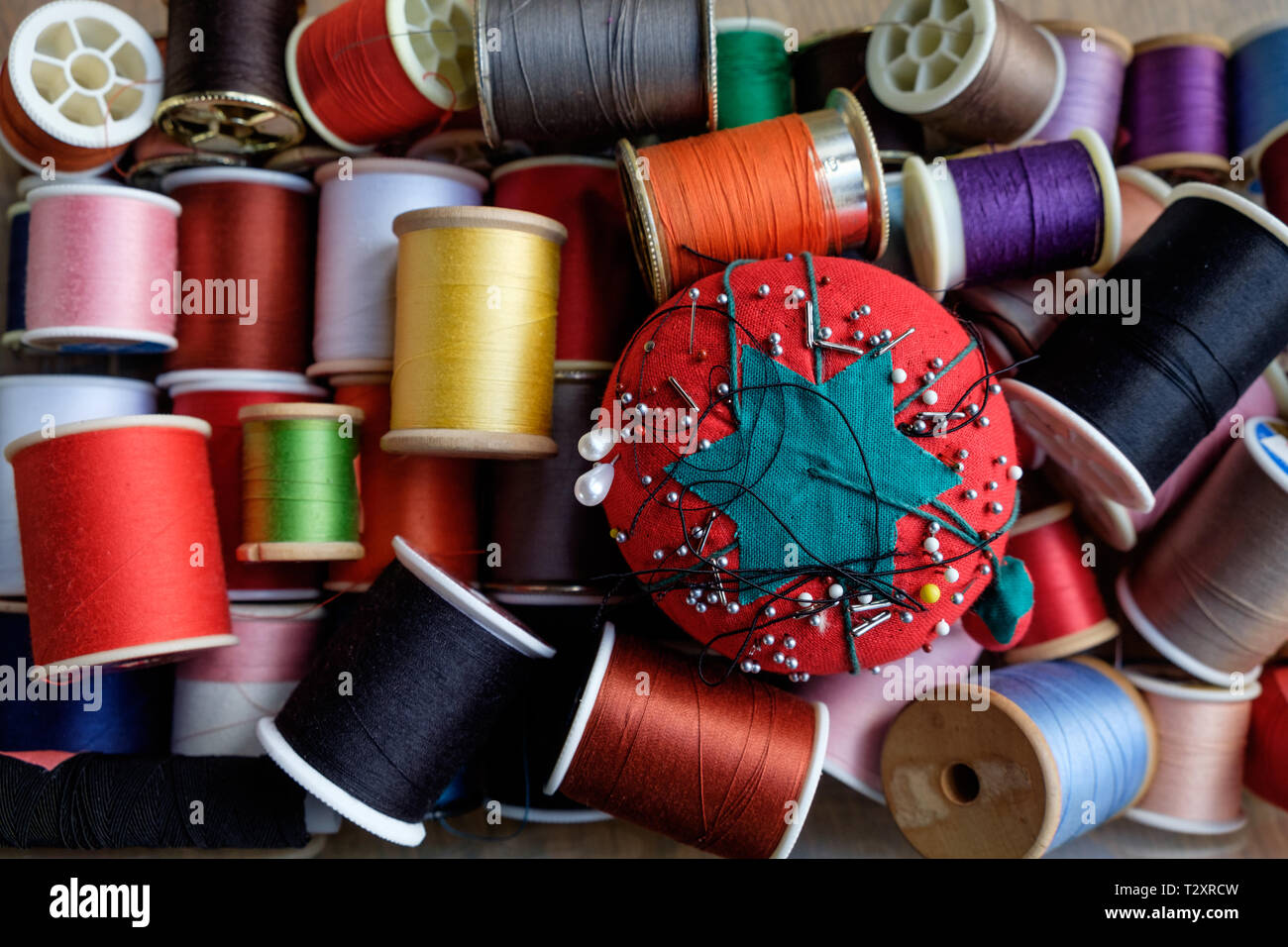 A tomato pin cushion with spools of colorful thread in a sewing kit. - Stock Image