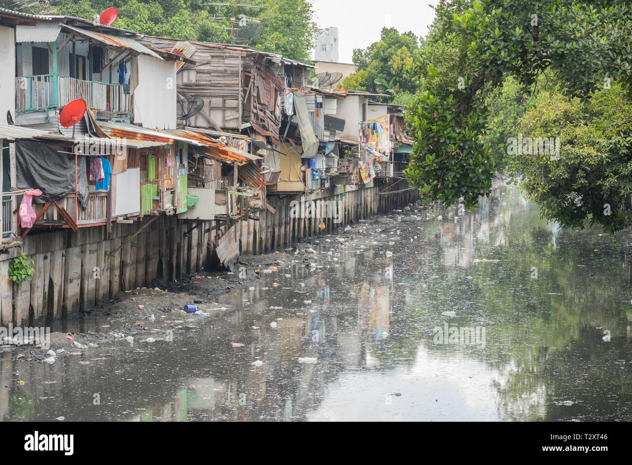 Bangkok, Thailand - September 25, 2018: slums along a smelly canal (Khlong Toei) full of mud and garbage in Khlong Toei District. - Stock Image