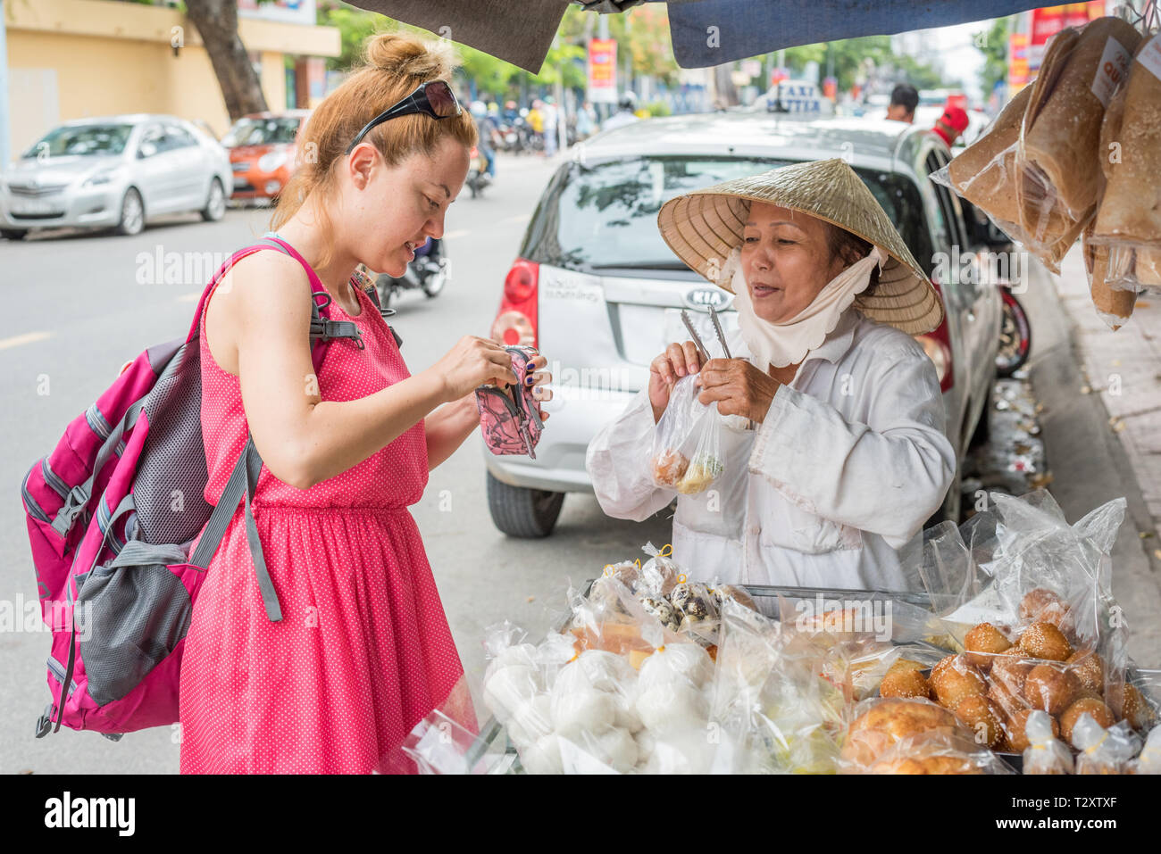 Nha Trang, Vietnam - May 5, 2018: A solo woman traveler buys sweets from a Vietnamese lady in an Asian conical hat who sells desserts out of her cart. Stock Photo