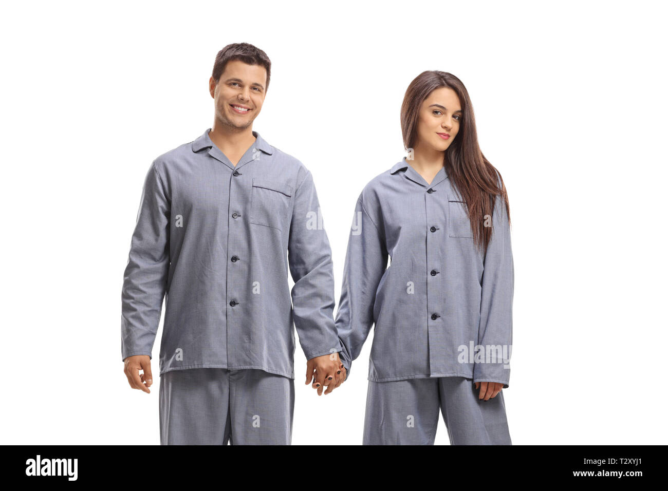 Young man and woman in pajamas holding hands isolated on white background - Stock Image
