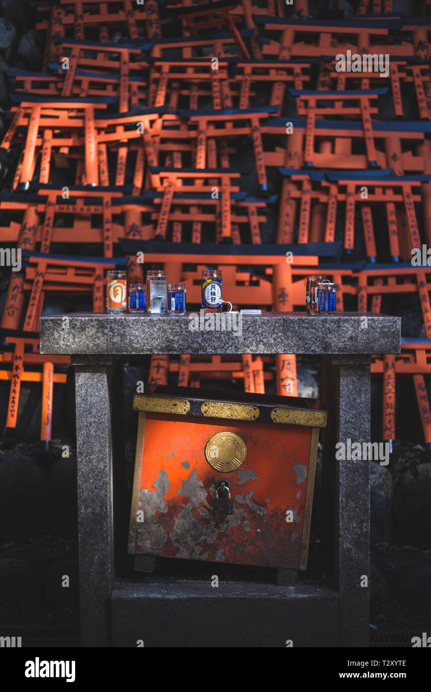 Small altar with torii gates in the background at Fushimi Inari shrine - Stock Image