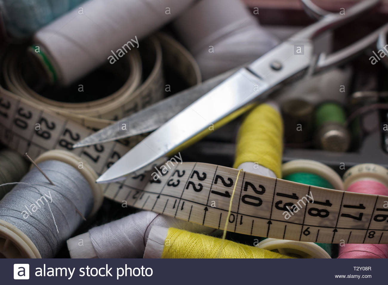 Colored threads, scissors and tape measure. Objects needed for a tailo - Stock Image