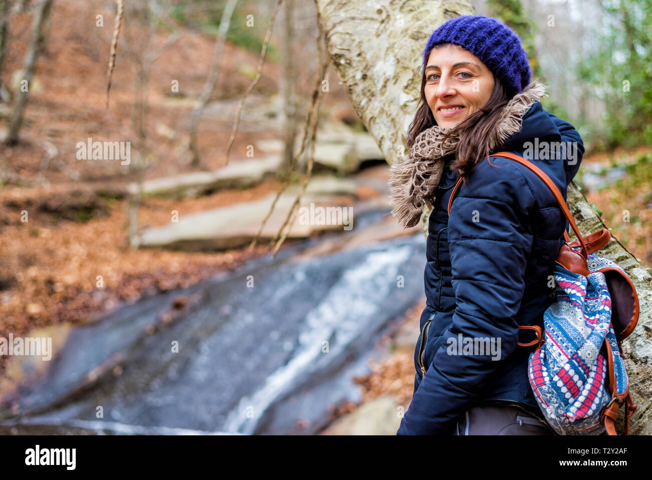 Woman looking to camera against falls in river wearing a wool hat and backpack - Stock Image