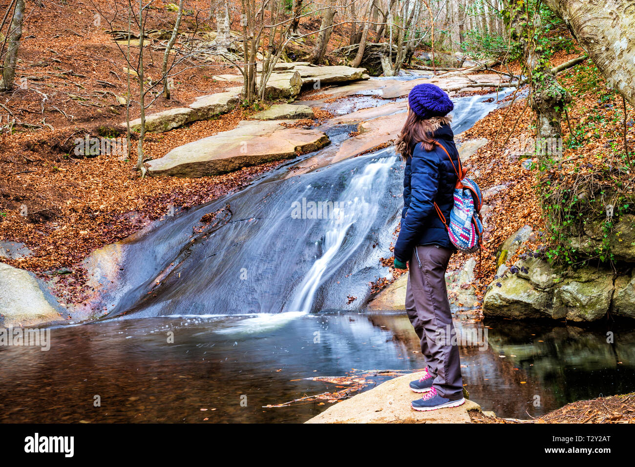 Woman standing watching falls in river - Stock Image