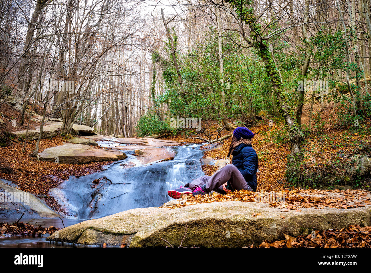 Woman sitting in the shore of the river admiring waterfall in the forest - Stock Image