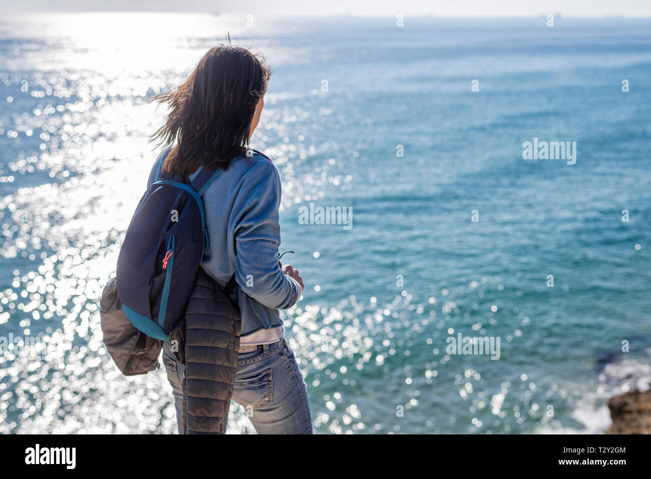 Rear view of a woman standing while contemplating the sea view - Stock Image
