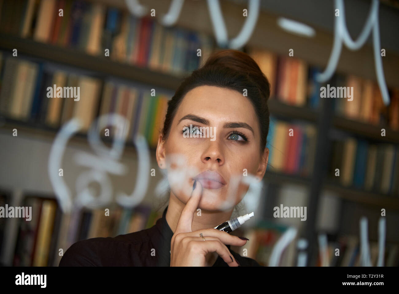Educated business woman writing down math formula on glass - Stock Image