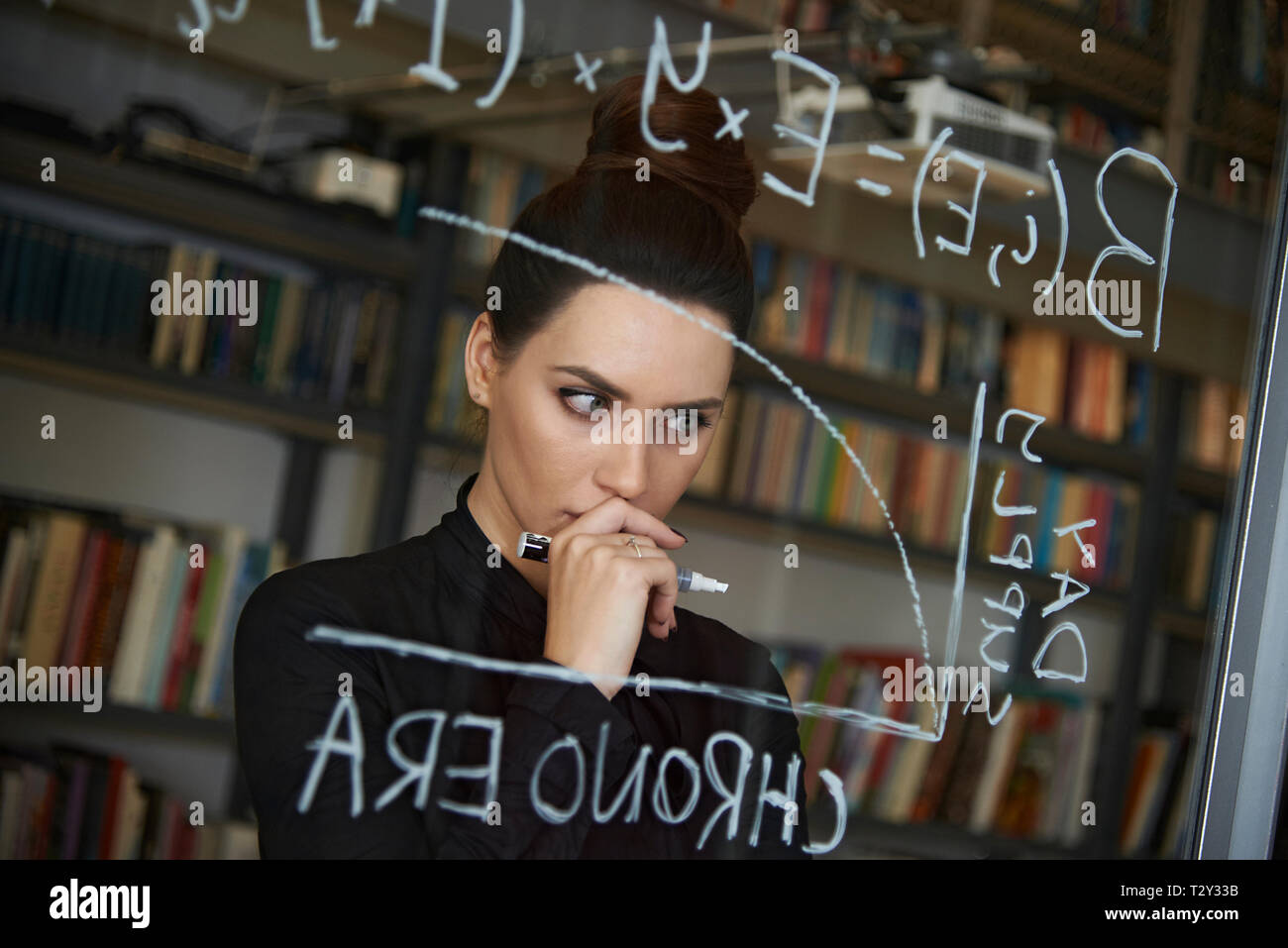 Educated business woman writing down mathmetical formula on glass - Stock Image