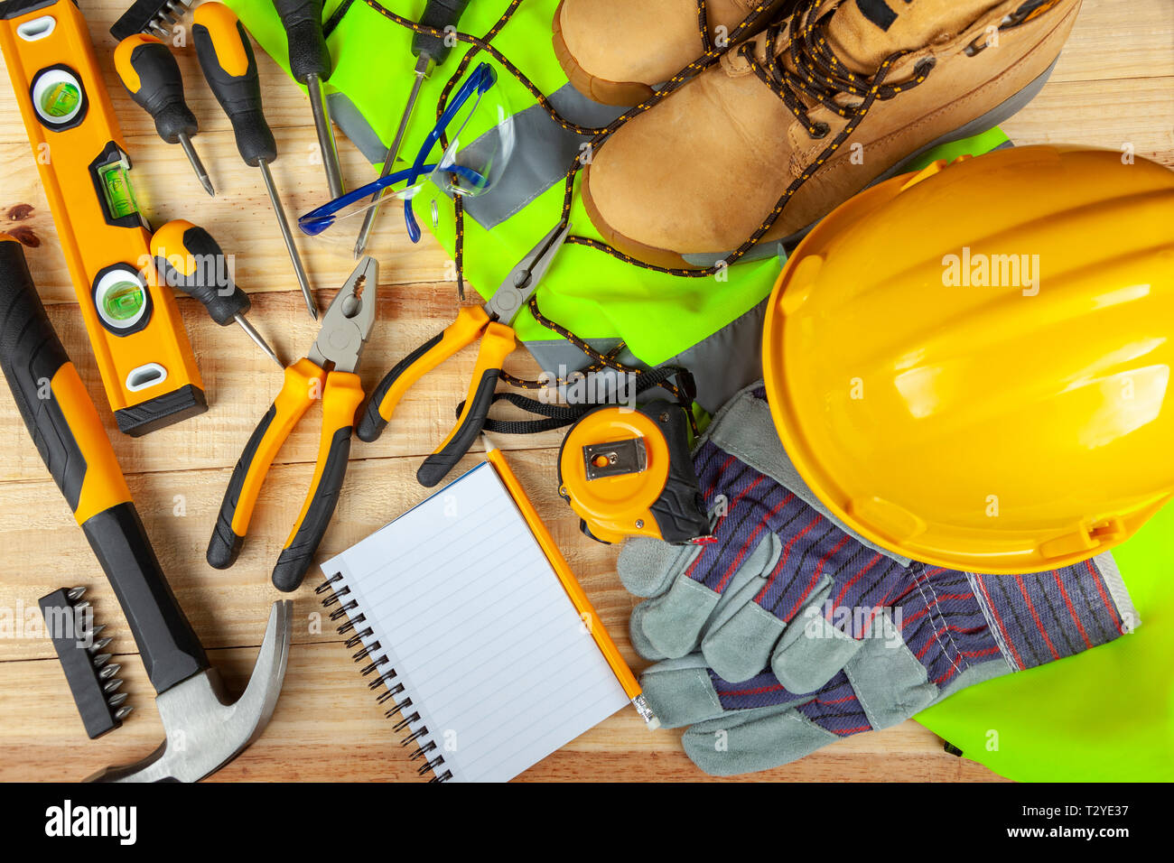 High visibility vest with work boots and yellow hard hat along side various hand tools on a work bench - Stock Image