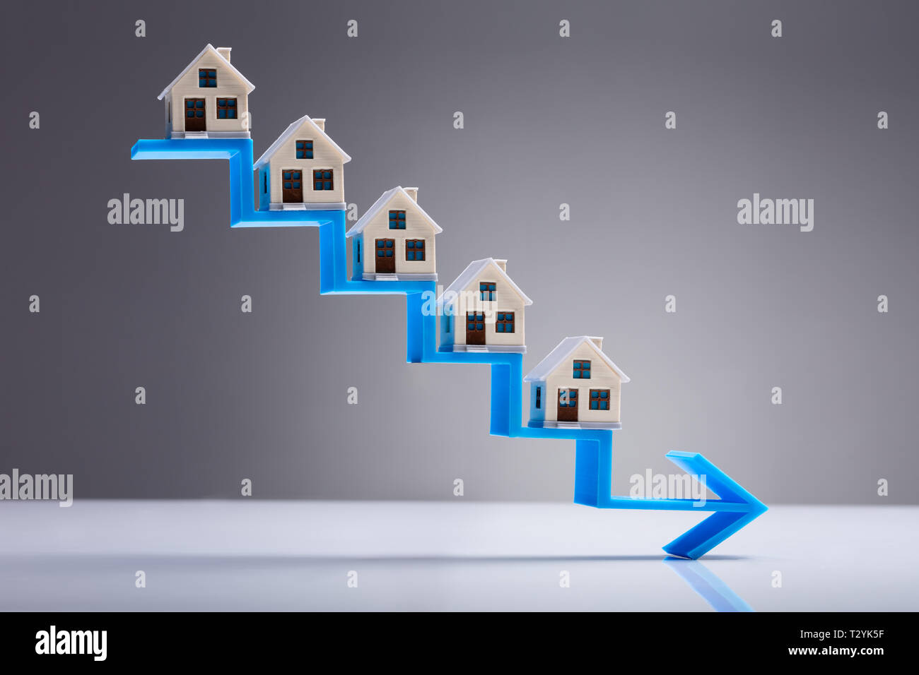 House Models On The Decreasing Staircase Blue Arrow Against Gray Background - Stock Image