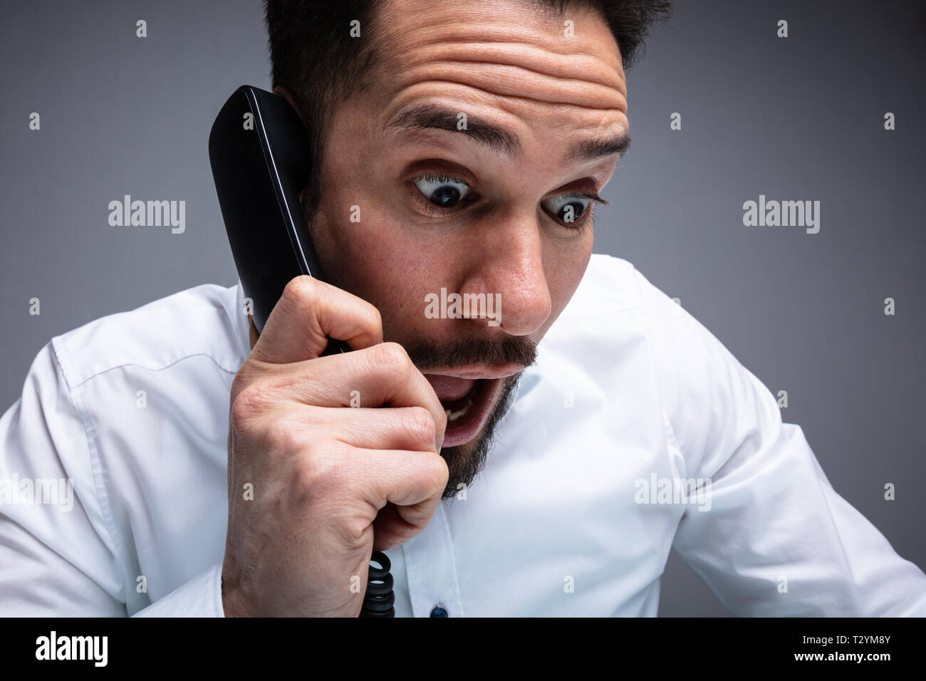 Close-up Of Frustrated Businessman Yelling An Phone - Stock Image