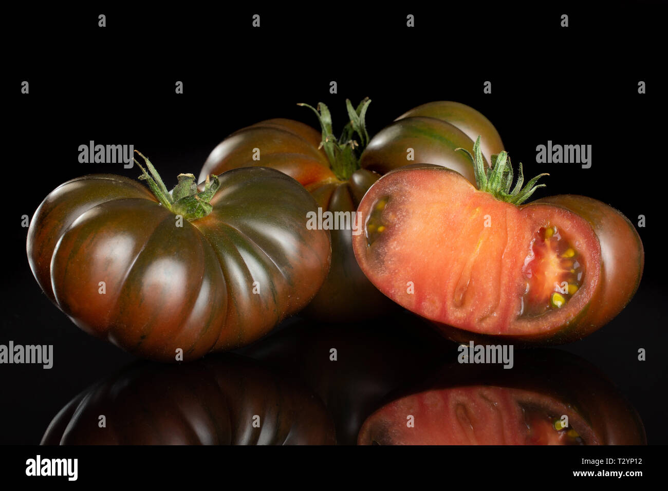 Group of two whole one half of fresh tomato primora isolated on black glass - Stock Image