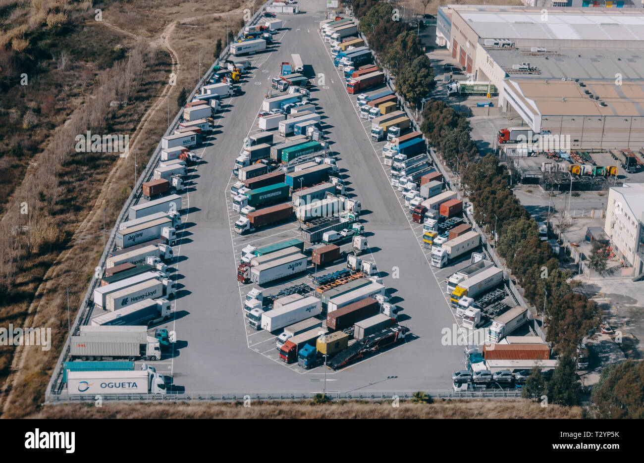 Haulage trucks sit parked in a distribution warehouse in an aerial photograph taken in public airspace over Zona Franca, Barcelona. - Stock Image