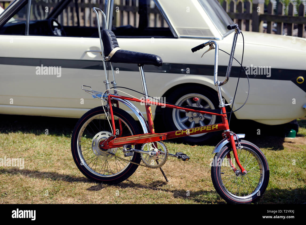 Raleigh Chopper bicycle standing beside a Ford Lotus Cortina - Stock Image