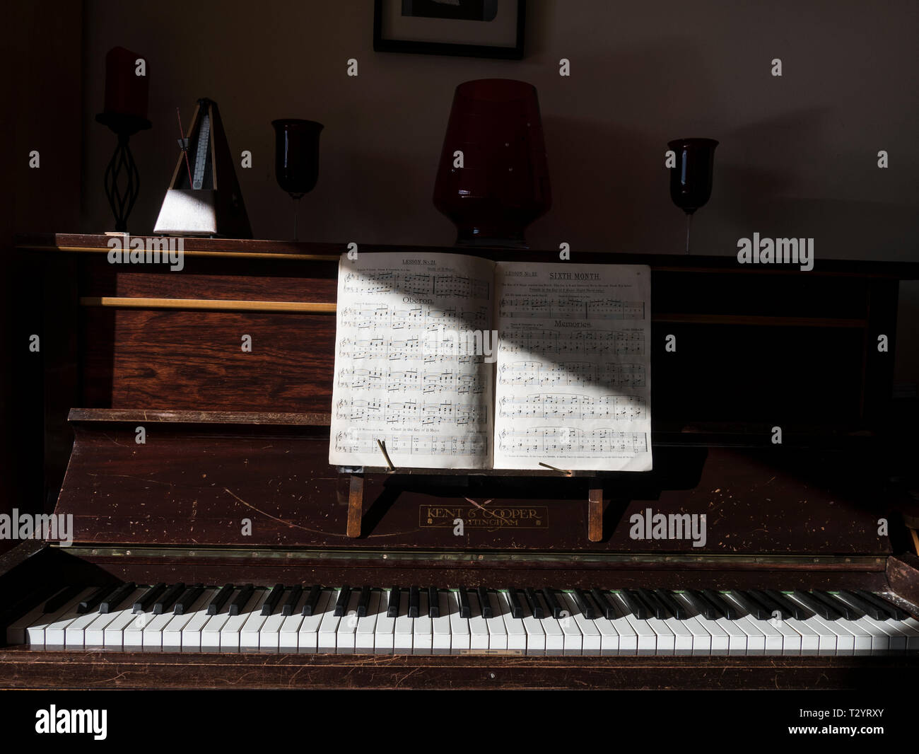 Sun falling across a music book open on an upright piano - Stock Image