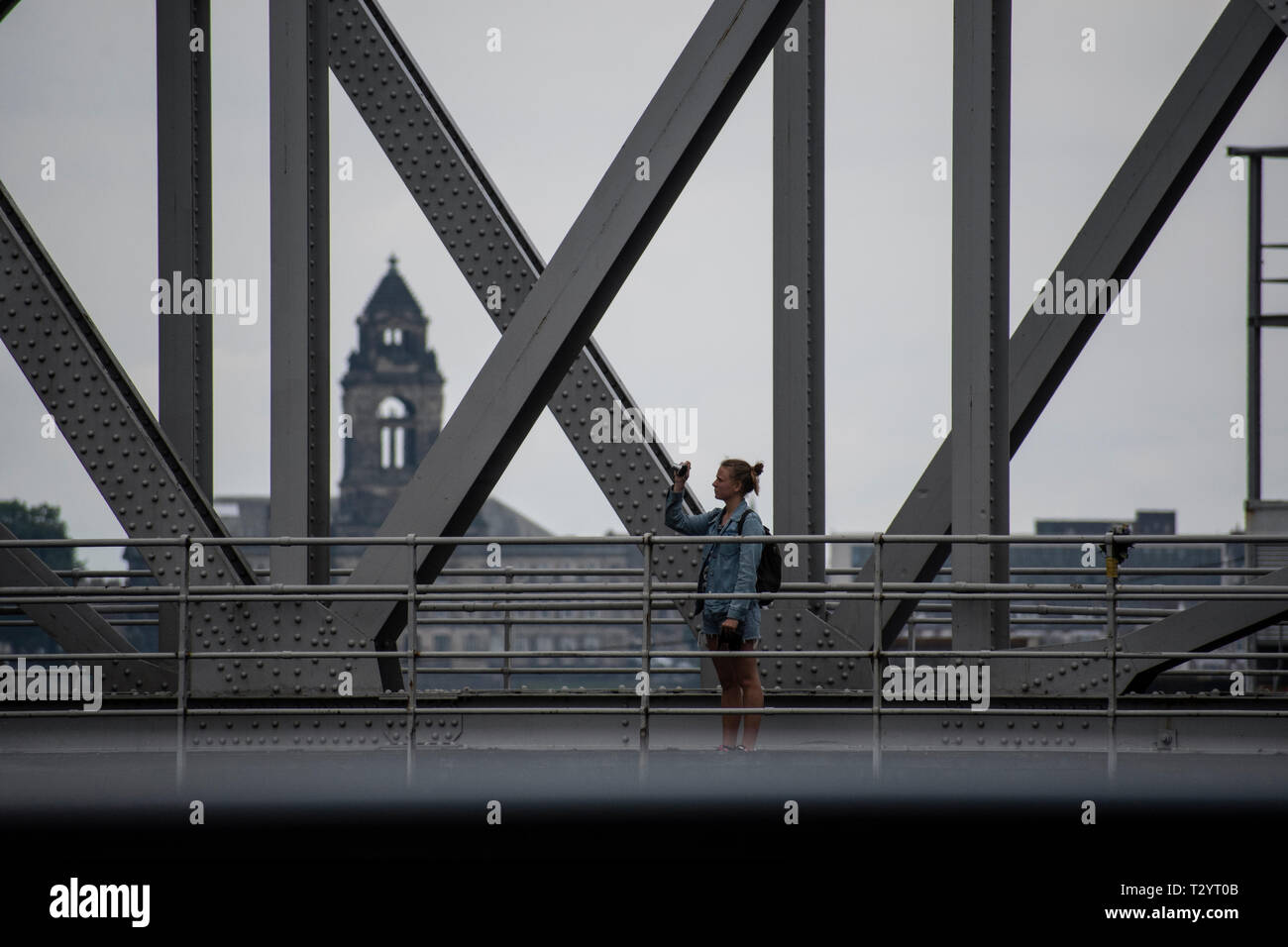 Young woman taking a photograph on Stanley Dock Bascule Bridge, Liverpool Stock Photo