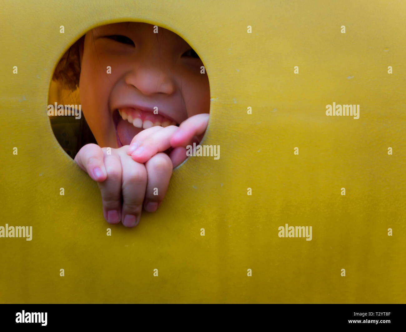 Asian little girl enjoys playing at children playground in leisure time - Stock Image