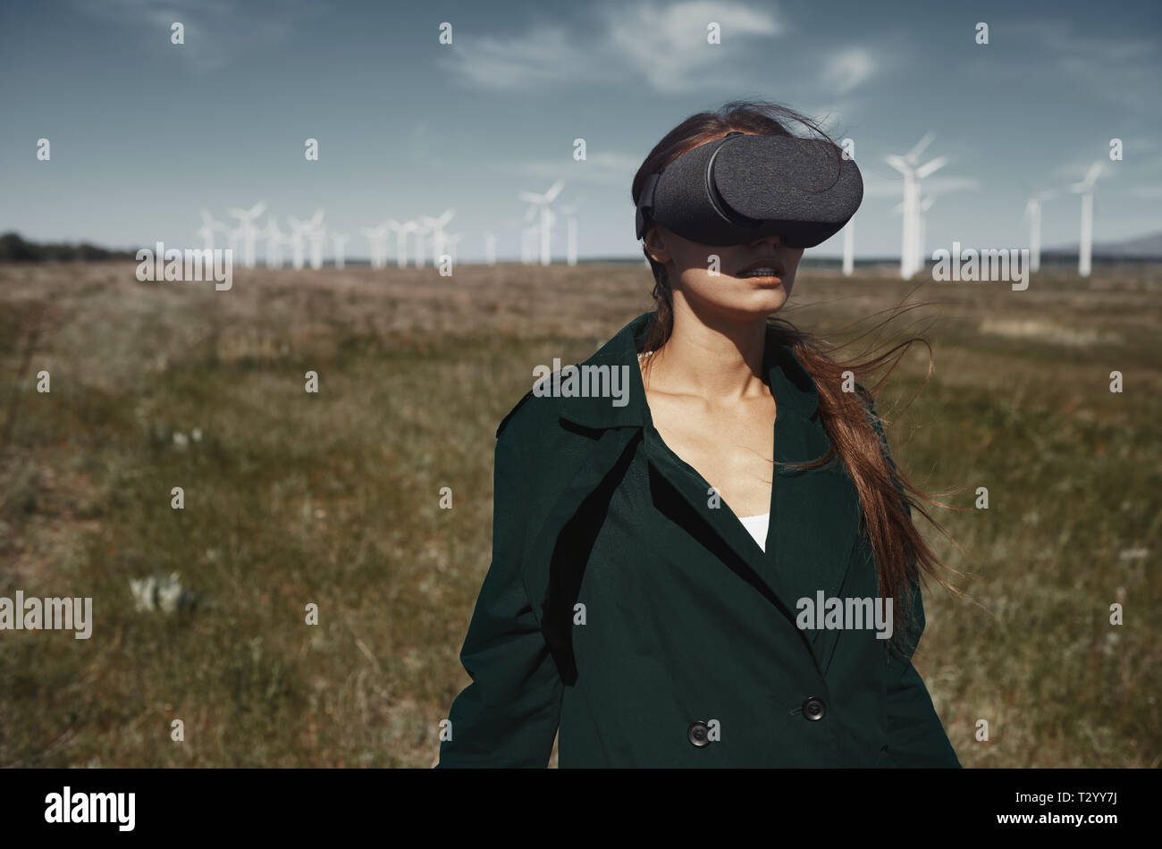 Woman wearing VR headset at the field next to the wind turbines Stock Photo