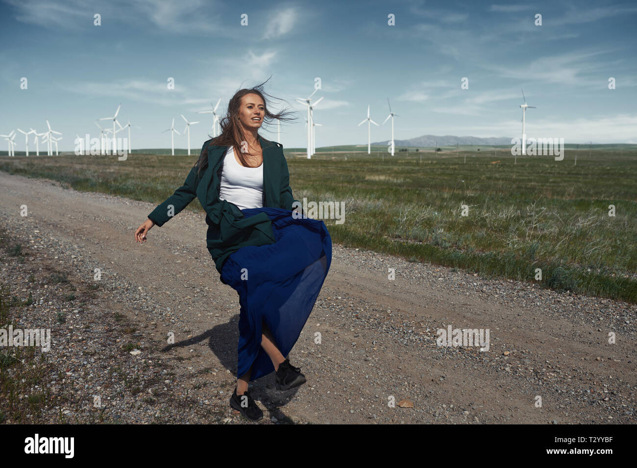 Woman with long tousled hair next to the wind turbine with the wind blowing Stock Photo