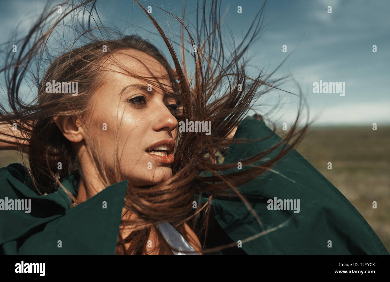 Woman outdoors with tousled wind blown hairs - Stock Image
