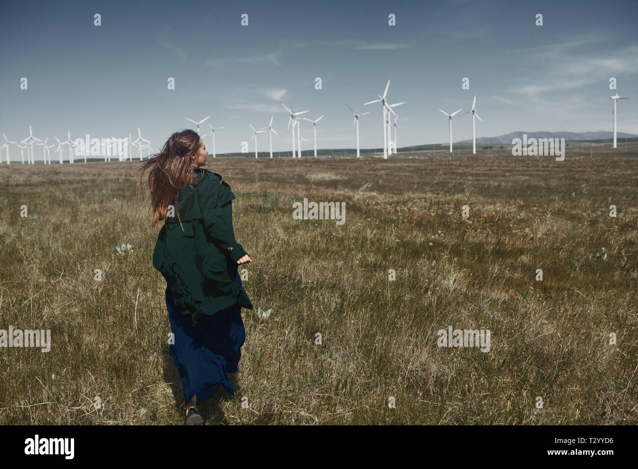 Woman with long tousled hair next to the wind turbine with the wind blowing - Stock Image