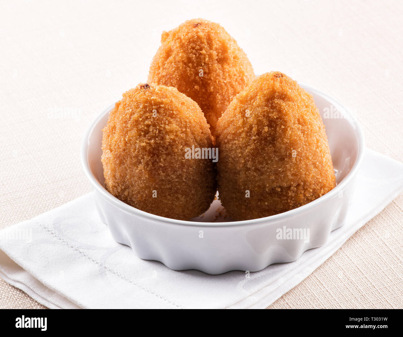 Three deep fried Arancini, breaded rice balls with a savory stuffing, from Sicily served in a bowl with white napkin - Stock Image