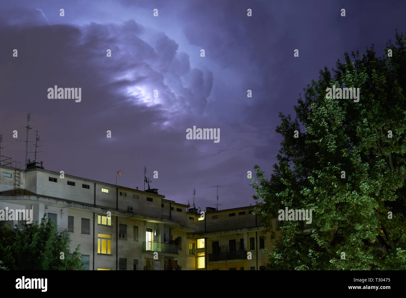 Buildings and green trees at night, illuminated sky during a lightning storm Stock Photo