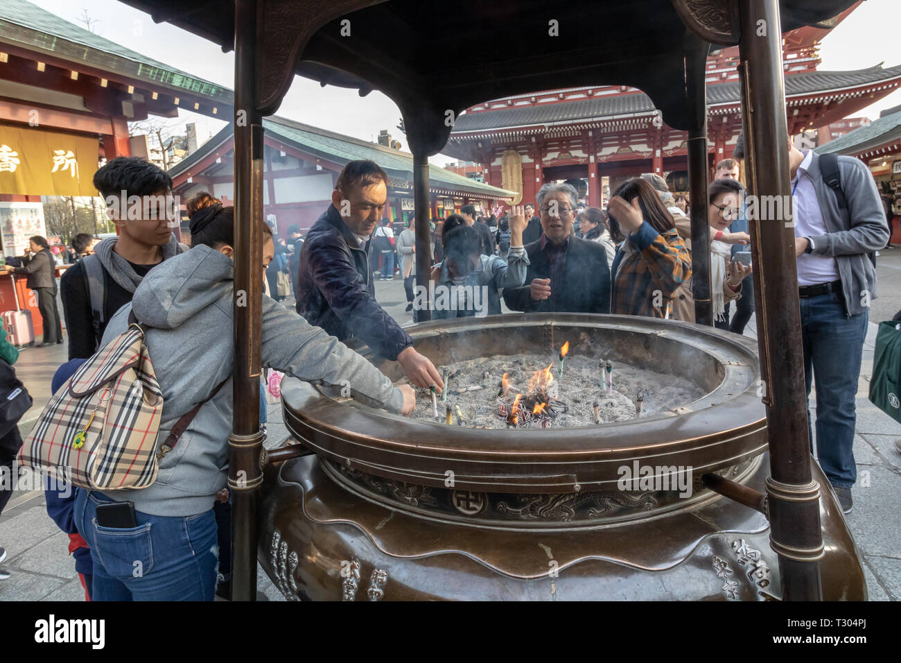 Tourists from all corners of the world come to Senso-Ji temple to purify themselves with what they believe to be a healing incense of Jokoro - Stock Image