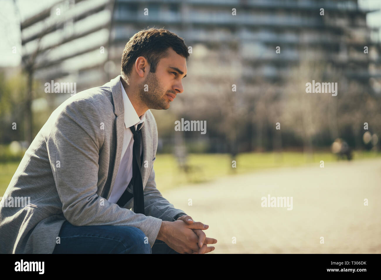 Young businessman is very tired. He is relaxing in park. - Stock Image