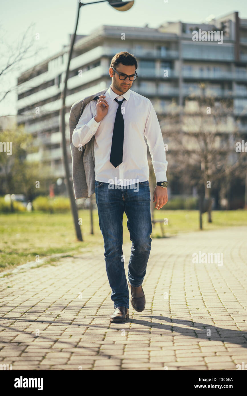 Young tired businessman is going home from work. - Stock Image