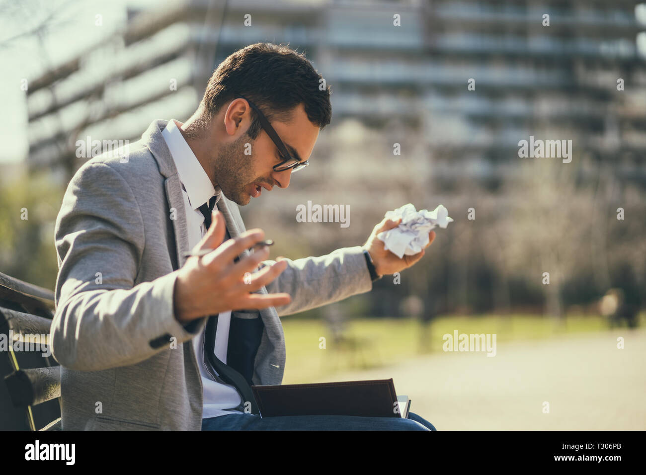 Young businessman is angry and overworked. - Stock Image
