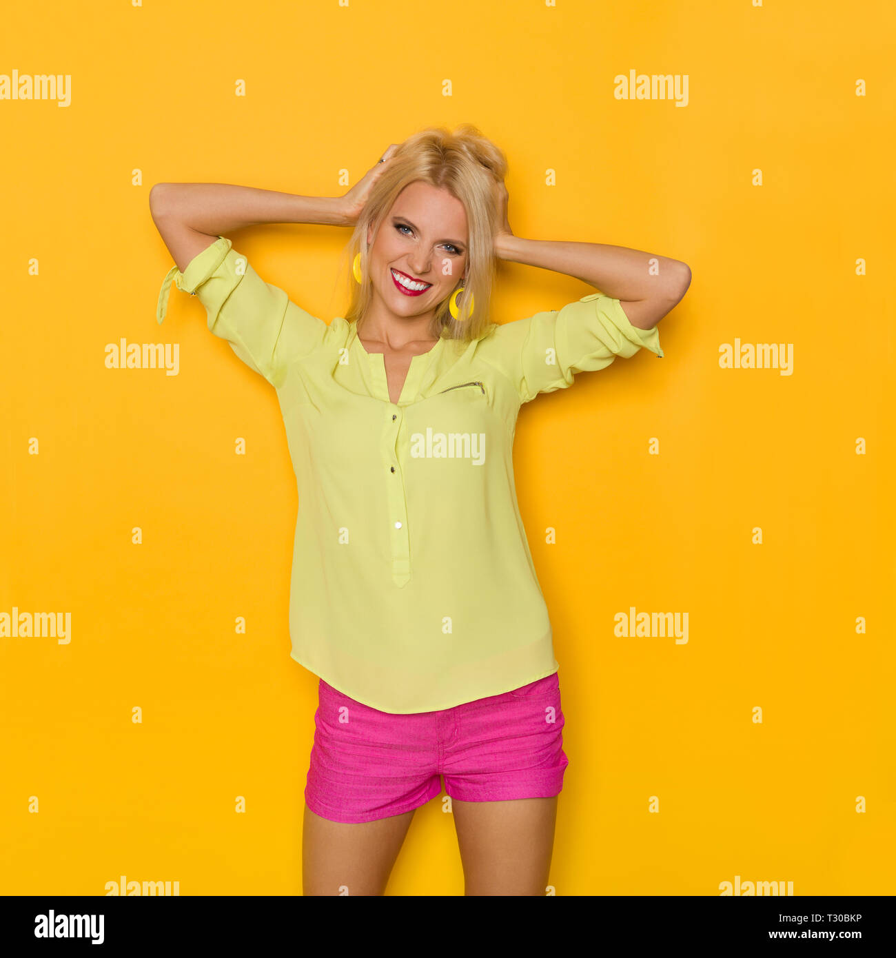 Cute blond young woman in yellow shirt and pink shorts is holding head in hands and smiling. Three quarter length studio shot on yellow background. - Stock Image