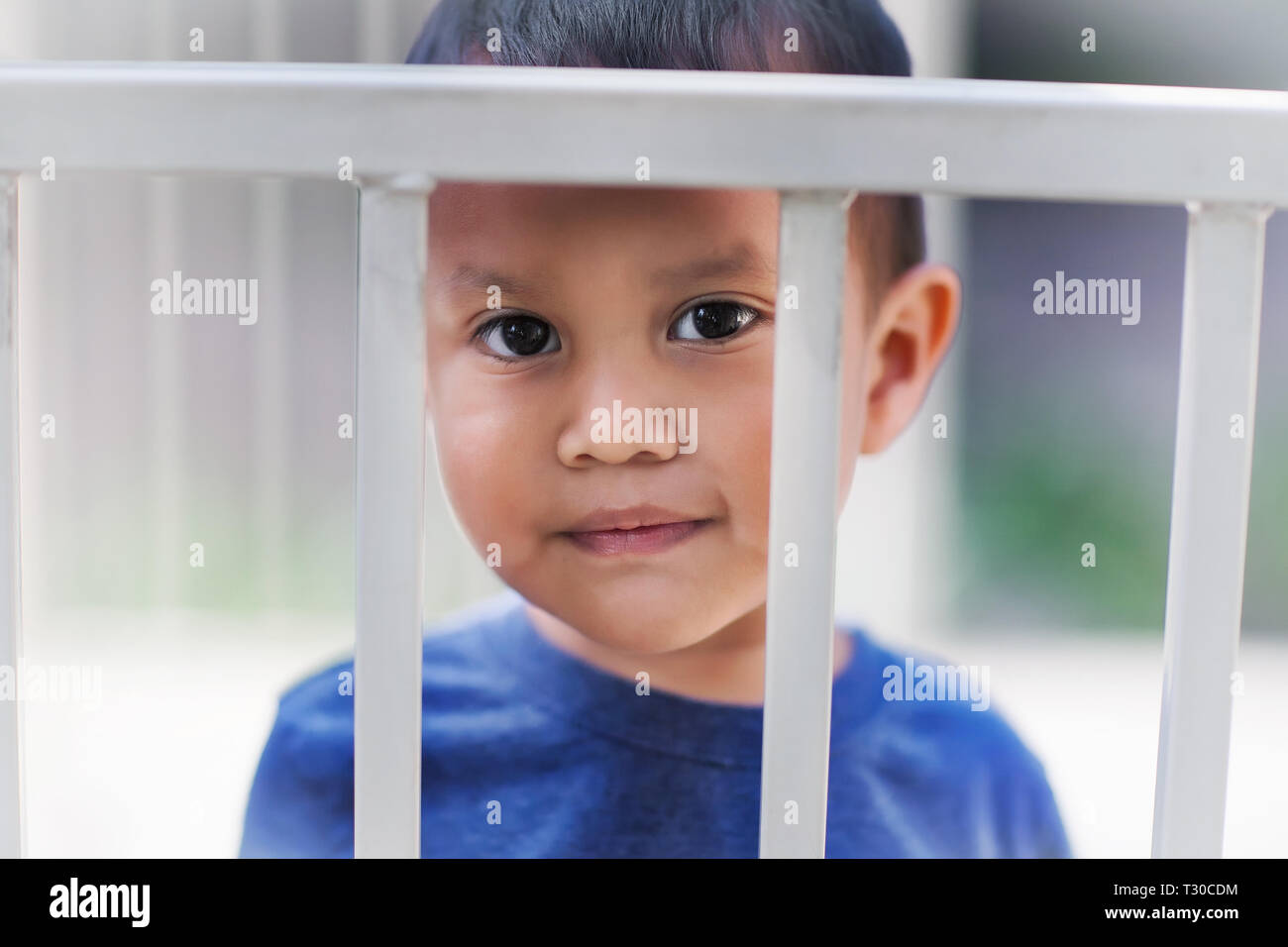 Young hispanic boy behind bars from a crib looking sad about getting a time out for bad behavior. - Stock Image