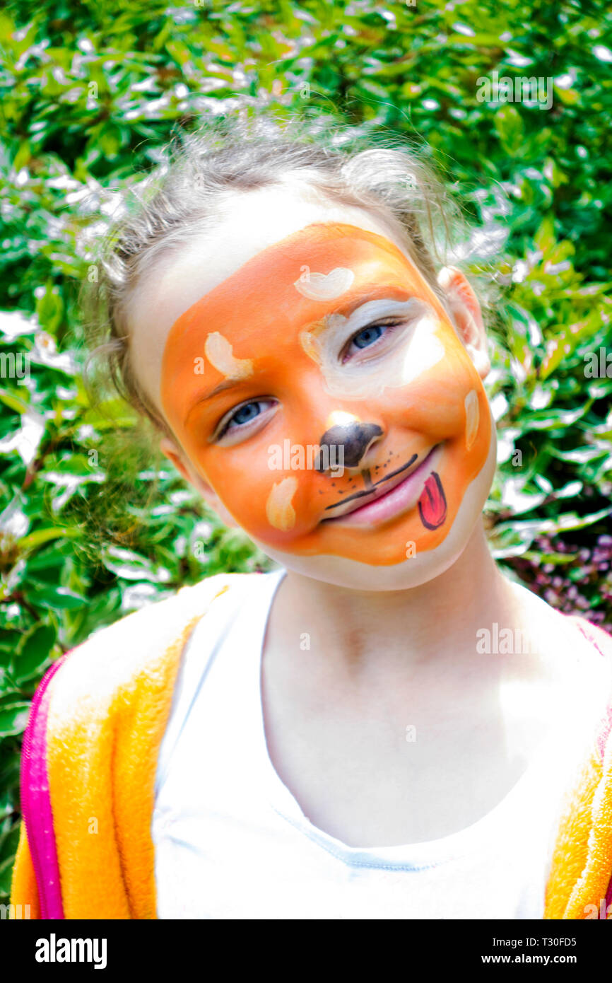 Young girl smiling with her face painted as a dog. - Stock Image