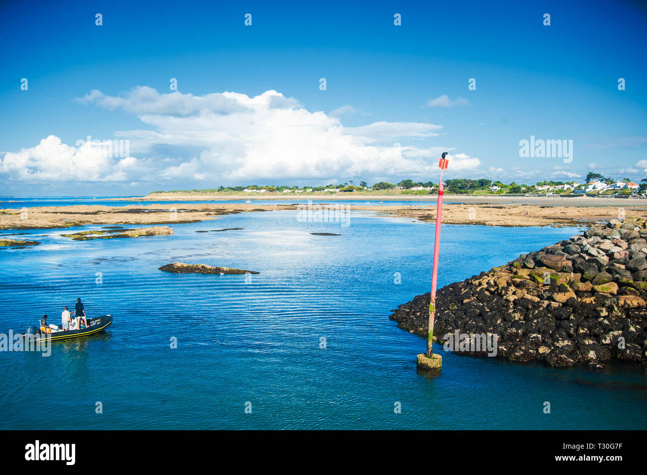 Cormoran on a pole at sea drying in the sun in Summertime on the isle of Noirmouiter with some people on a little boat - Stock Image