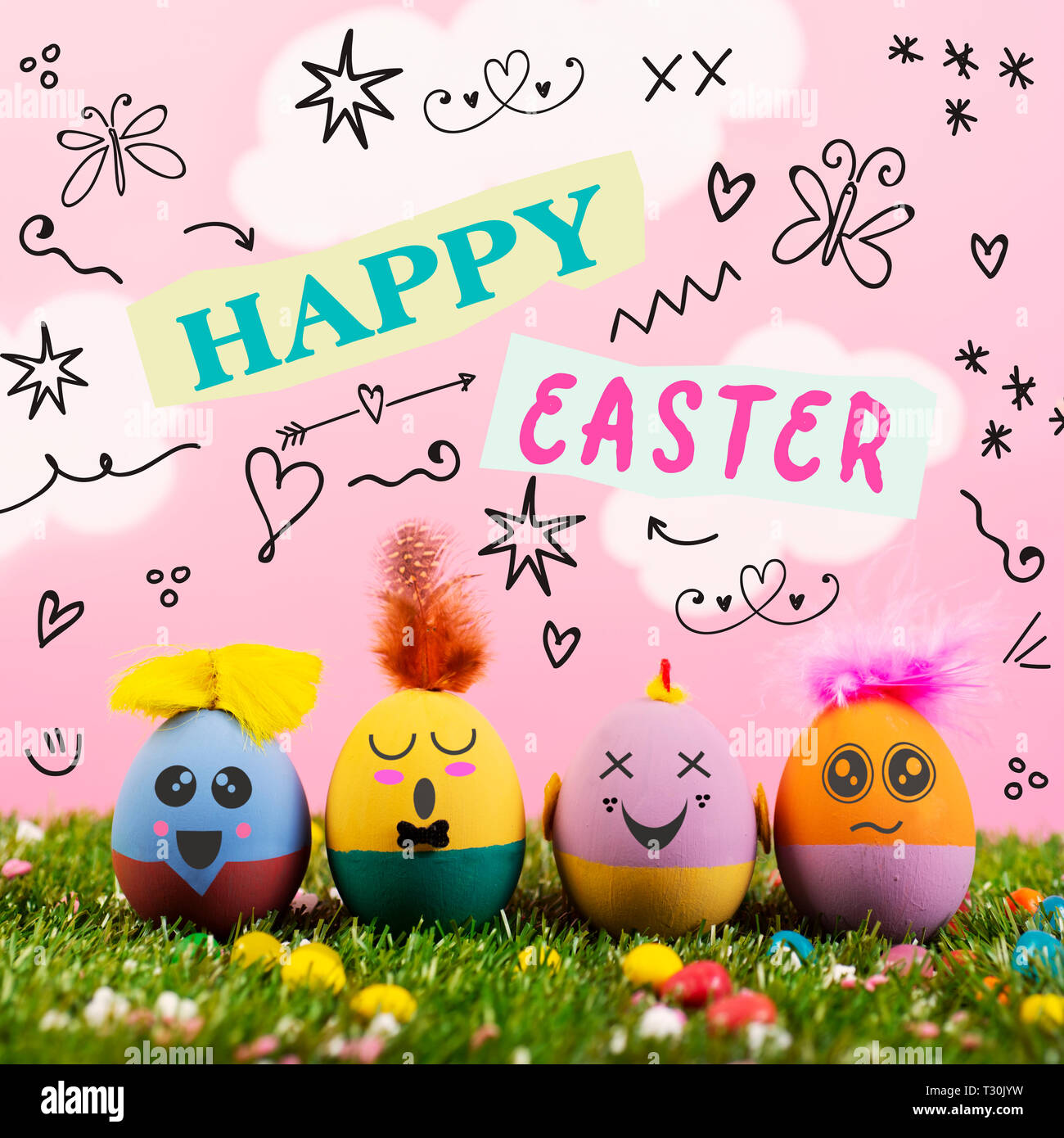 text happy easter, as paper cutouts, and some handmade easter eggs, with cute and funny faces, on the grass with a pink sky with white clouds in the b Stock Photo