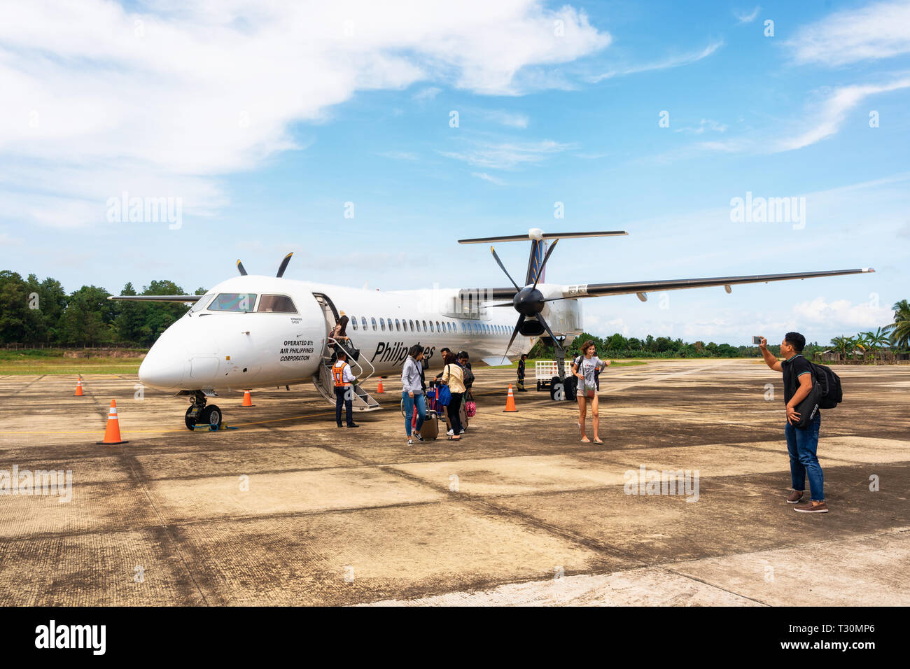 San Vicente, Philippines - January 30, 2019: Travellers leave Bombardier Q400 airplane Philippine Airlines at new small Airport in Palawan Island. - Stock Image