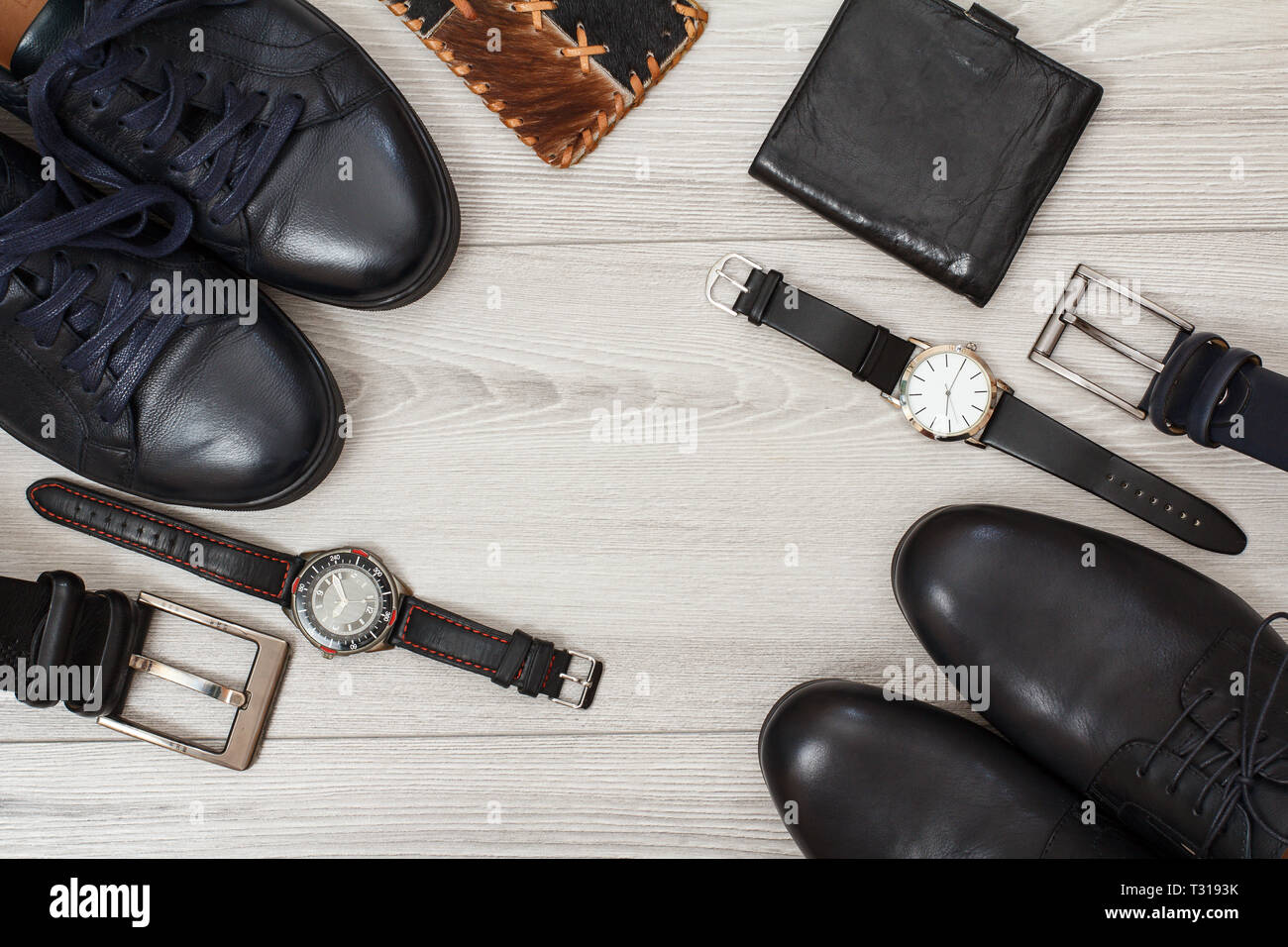 Two pairs of black leather men's shoes, two belts for men, wallets and wristwatches on gray wooden background. Men's accessories. Top view. - Stock Image