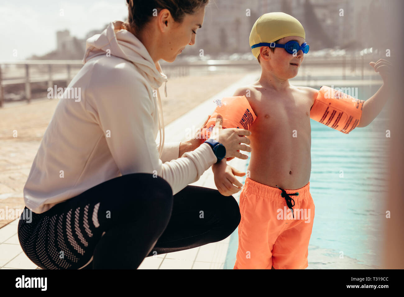 Female coach helping boy put on sleeve floats by poolside. Woman putting sleeves floats on boy's hand for swimming lessons at pool. Stock Photo